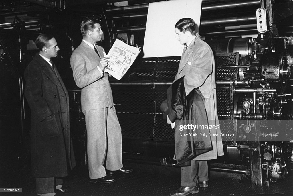 Clark Gable reads the Daily News hot off the press. : News Photo