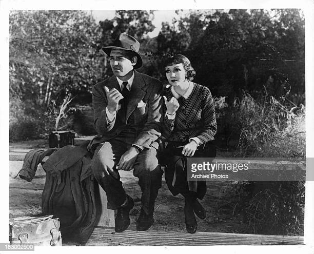 Clark Gable sits on a bench with Claudette Colbert in a scene from the film 'It Happened One Night' 1934
