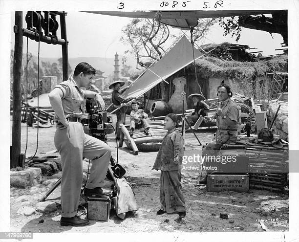Clark Gable standing next to film equipment as Chinese boy speaks to him in a scene from the film 'Too Hot To Handle' 1938