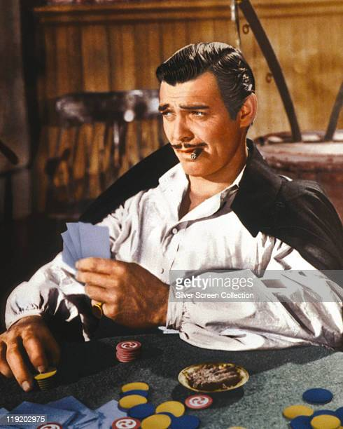 Clark Gable US actor playing cards and smoking a cigar in a publicity still issued for the film 'Gone With The Wind' USA 1939 The 1939 drama directed...