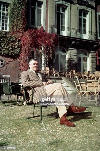 Clark Gable US actor wearing a tweed jacket beige trousers and brown suede shoes relaxing with his legs crossed in a chair in a garden circa 1950