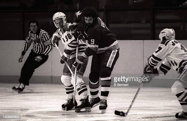Clark Gillies of the New York Islanders and Robbie Ftorek of the New York Rangers battle for the puck as Ftorek's teammate Eddie Johnstone controls...