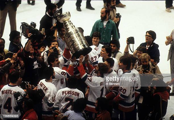 Clark Gillies of the New York Islanders hands the Stanley Cup Trophy to teammate Greg Gilbert after defeating the Edmonton Oilers in Game 4 of the...