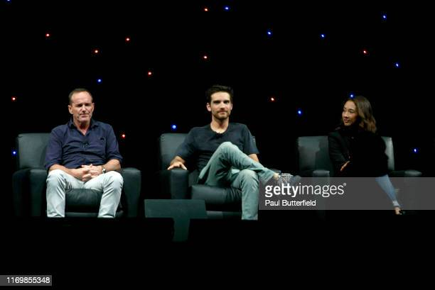 """Clark Gregg, Jeff Ward, and Maurissa Tancharoen speak at Marvel's """"Agents of S.H.I.E.L.D."""" panel during the 2019 D23 Expo at Anaheim Convention..."""