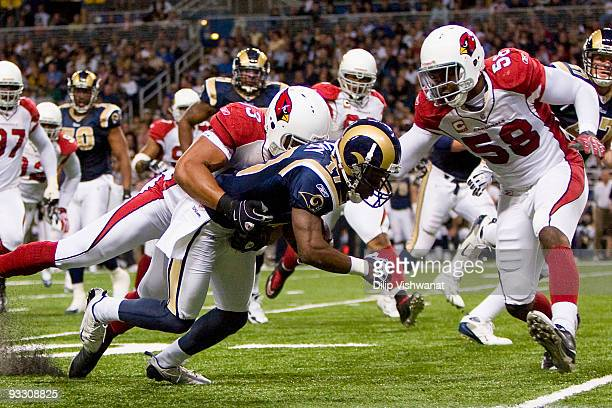 Clark Haggans and Karlos Dansby both of the Arizona Cardinals tackle Donnie Avery of the St Louis Rams at the Edward Jones Dome on November 22 2009...
