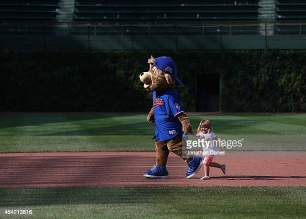 'Clark' the macot of the Chicago Cubs runs the bases with a small child after a game against the Baltimore Orioles at Wrigley Field on August 24 2014...