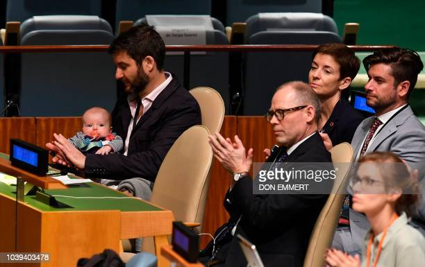 Clarke Gayford claps holding his daughter Neve Te Aroha Ardern Gayford as his partner Jacinda Ardern Prime Minister and Minister for Arts Culture and...