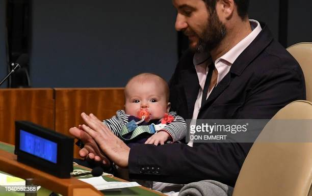 TOPSHOT Clarke Gayford claps holding his daughter Neve Te Aroha Ardern Gayford as his partner Jacinda Ardern Prime Minister and Minister for Arts...