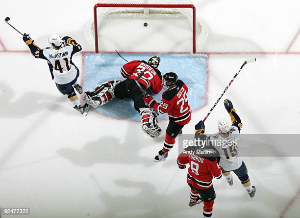 Clarke MacArthur and Tim Connolly of the Buffalo Sabres celebrate a goal as Martin Brodeur Johnny Oduya and Dainius Zubrus of the New Jersey Devils...