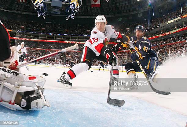 Clarke MacArthur of the Buffalo Sabres and Matt Carkner of the Ottawa Senators chase a rebound in front of goaltender Brian Elliott of the Senators...