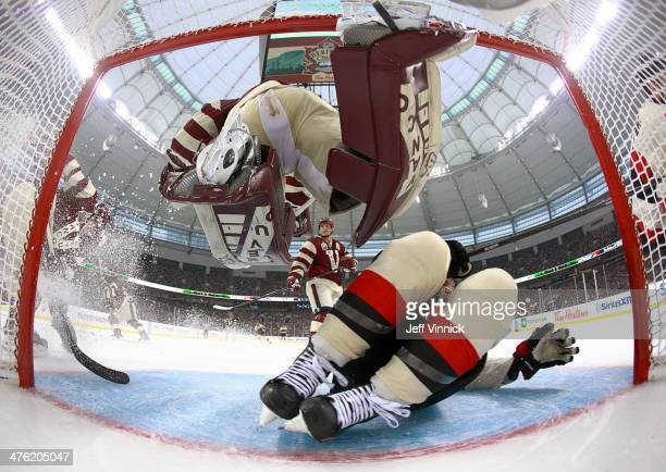 Clarke MacArthur of the Ottawa Senators slides into Eddie Lack of the Vancouver Canucks during the 2014 Tim Hortons NHL Heritage Classic at BC Place...