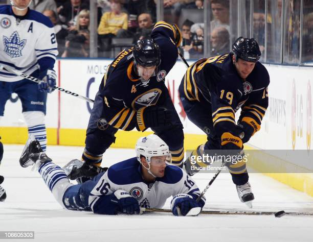 Clarke MacArthur of the Toronto Maple Leafs struggles to control the puck against Steve Montador and Tim Connolly of the Buffalo Sabres at the Air...
