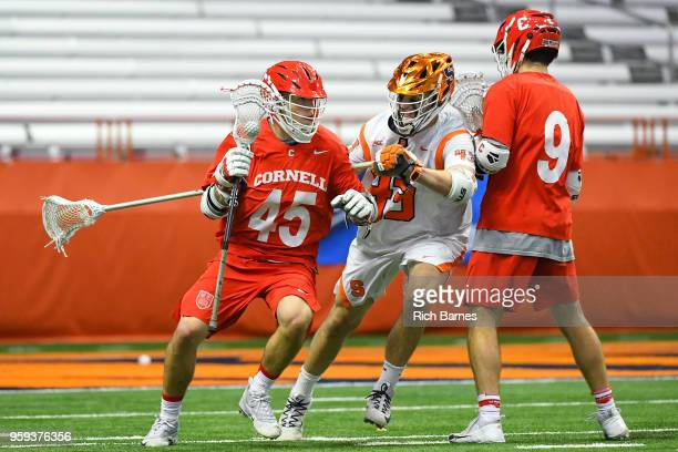Clarke Petterson of the Cornell Big Red dodges to the goal against the defense of Marcus Cunningham of the Syracuse Orange during a 2018 NCAA...