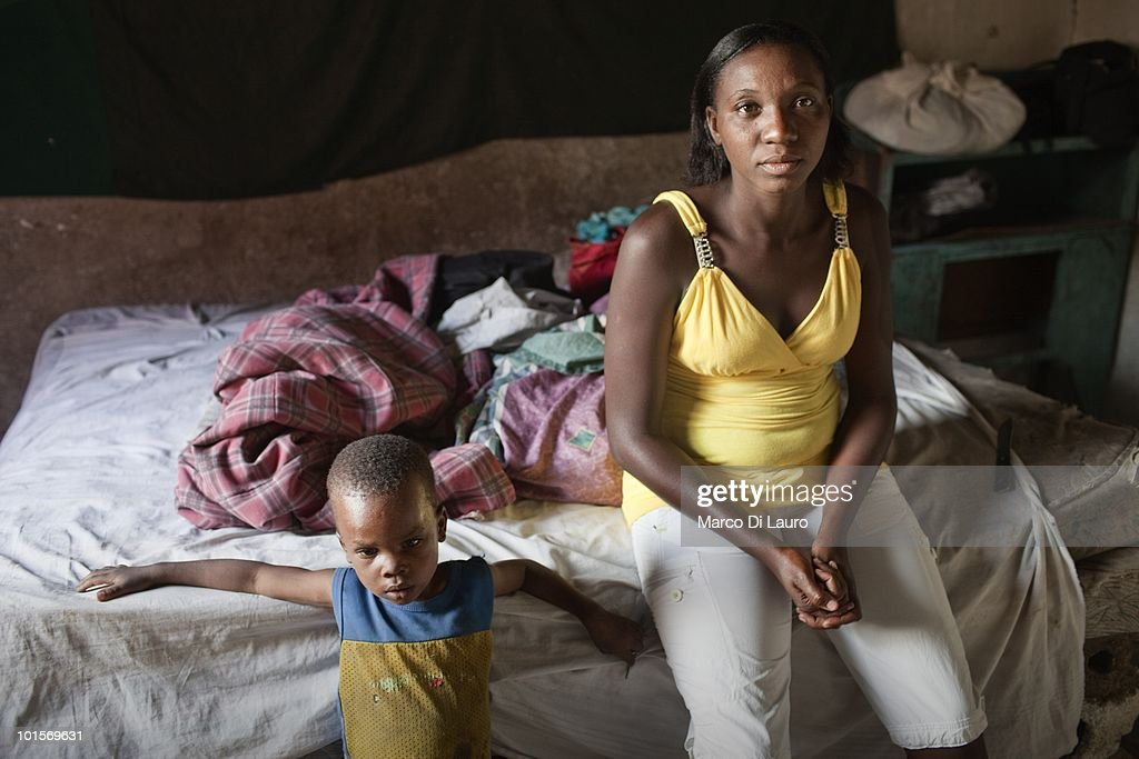 Clarmante Petit Tomb, 26-years-old is seen with 5-years-old Johnlee at her makeshift house in what was a school in a temporary camp on February 2, 2010 in Port Au Prince, Haiti. Clarmante camps in the park next to the National Theatre. She is taking care of five-years-old Johnlee, her niece's brother, not related to her by blood. She has no incomeand worries she will have to put Johnlee into a orphangae if someone doesn't help her to support him. Johnlee is actually malnourished. He rarely smiles. As many as 200,000 people died on January 12 as a consequence of the 7.0-magnitude earthquake. At least 130 people have been pulled alive from the rubble. An estimated 1.5 million people have been left homeless. The Haitian government is planning to relocate some 400,000 people, currently in makeshift camps across the capital, to temporary tent villages outside the city. Aid agencies are still struggling to supply food and water to survivors, while thousands of Haitians who suffered serious injuries remain in need of urgent medical attention.