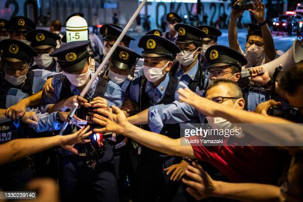 Clash between anti-Olympics protesters and police officers is seen during a protest to mark the opening ceremony of Tokyo Olympics on July 23, 2021...