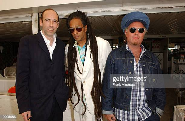 """Clash guitarist Mick Jones , directors Don Letts, and Rick Elgood pose at a cocktail party for the film """"Bright Young Things"""" at the Cannes Beach..."""
