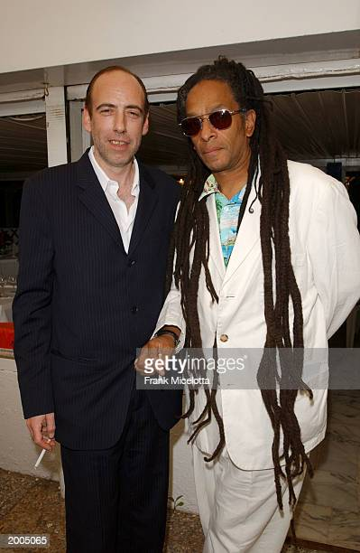 """Clash guitarist Mick Jones talks with director Don Letts at a cocktail party for the film """"Bright Young Things"""" at the Cannes Beach Restaurant during..."""