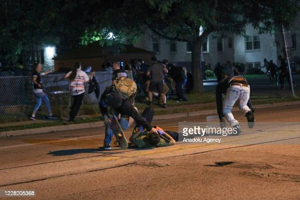 Clashes between protesters and armed civilians, who protect the streets of Kenosha against the arson, break out during the third day of protests over...