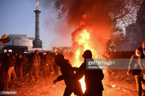 Clashes erupt as smoke and flares rise after a demonstration against the newly passed controversial global security law, in Paris, France, on...