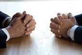 Clasped hands of two businessmen negotiators opponents opposite on table