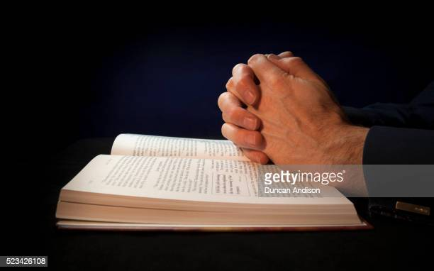 clasped hands on a bible while praying to god - image stock pictures, royalty-free photos & images