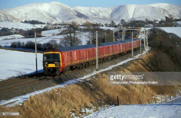 A Class 325 with a Royal Mail train speeds through the winter landscape at Docker in Cumbria February 2003