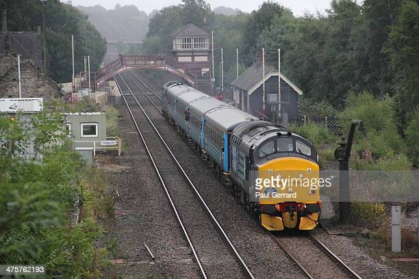 Class 37 diesel locomotive hauls charity train from Newcastle to Carlisle through Haltwhistle Station in Cumbria