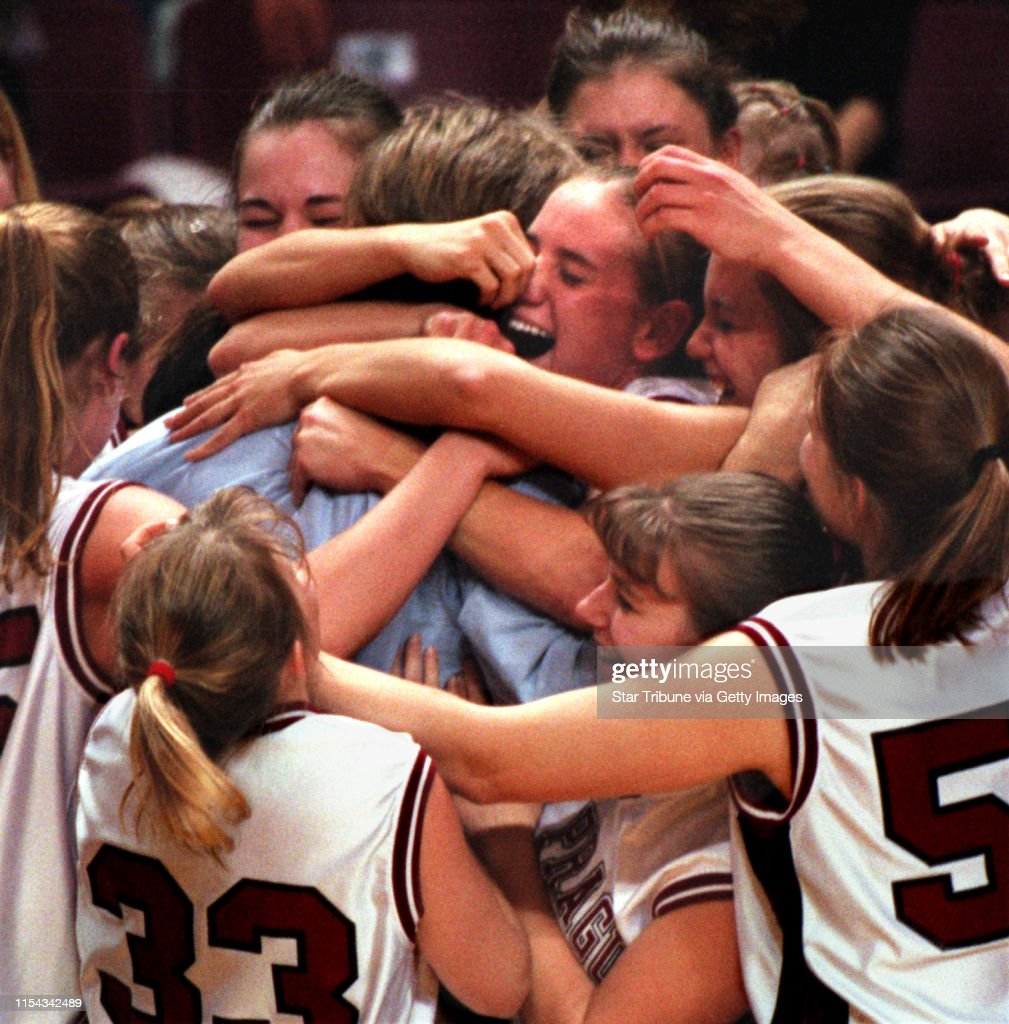 Class 3A girls' baskeball championship game Minneapolis North Polars vs. New Prague. -- New Prague head girls basketball coach Ron Gunderson (in blue shirt) is hugged by members of the team moments after they defeated Minneapolis North for the 3A title. : News Photo