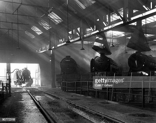Class 8F 2-8-0 no 48065 takes water outside the Roundhouse at York, whilst inside Class V2 2-6-2 no 60855; Class A1 4-6-2 no 60138 ?Boswell?; and...