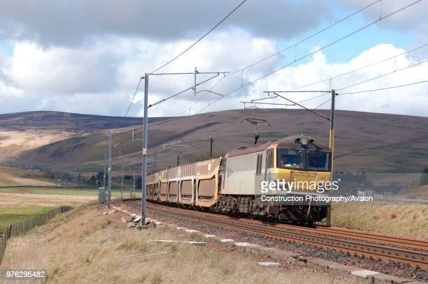 A Class 92 multivoltage electric locomotive curves through the Upper Clyde valley on the ascent of Beattock with a Mossend Carlisle Enterprise...