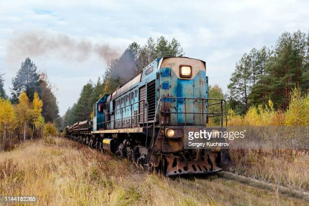 TEM2U class diesel locomotive leads dump cars train loaded with sand from the quarry