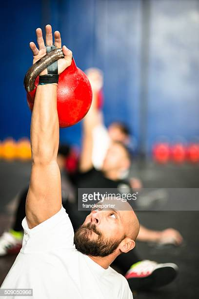 class lifting a kettlebell in a gym - sports equipment stock pictures, royalty-free photos & images