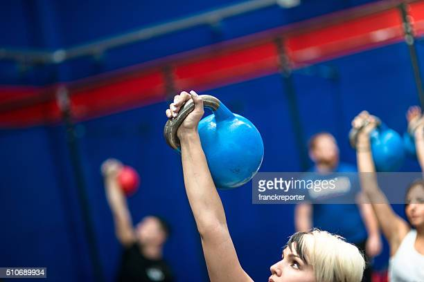 class lifting a kettlebells in a gym - skinny man fat woman stock pictures, royalty-free photos & images