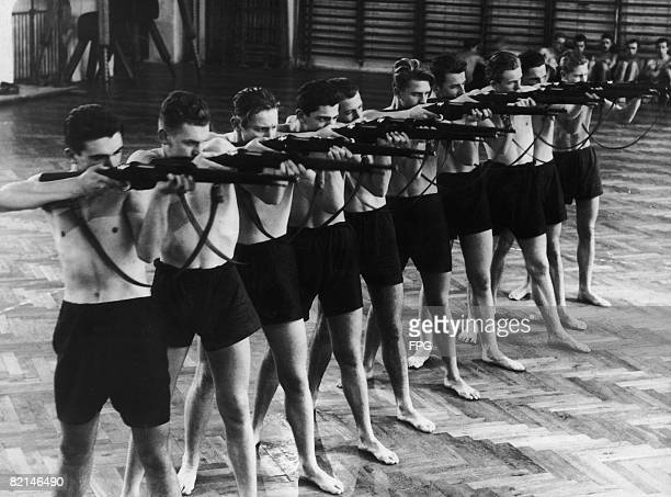 A class of boys at a secondary school in Vienna being trained in the use of firearms circa 1939 Premilitary training has been mandatory in Austrian...