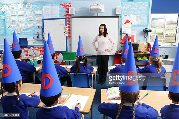 class of children wearing dunce hats - dunce cap stock pictures, royalty-free photos & images