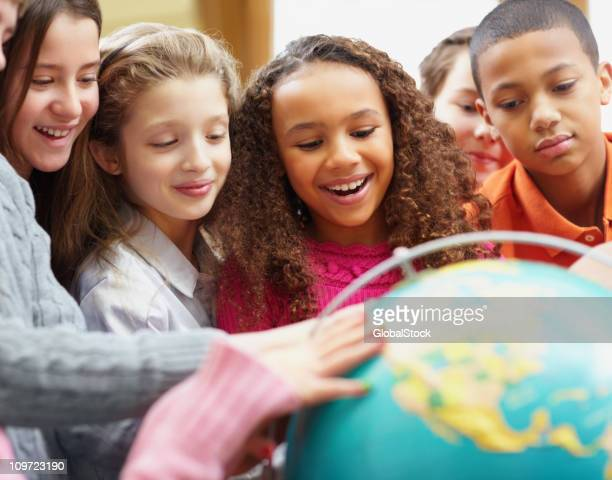 class of geography students looking at a globe - 10 11 jaar stockfoto's en -beelden