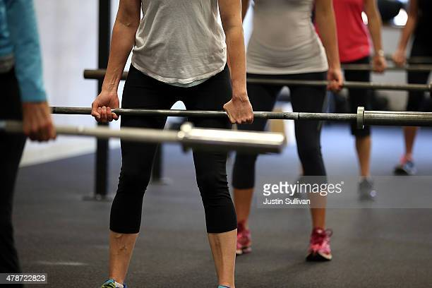 Class participants warm up with a bar bell during a CrossFit workout at Ross Valley CrossFit on March 14, 2014 in San Anselmo, California. CrossFit,...