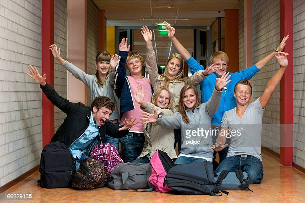 class photo of cheering high school students in hallway