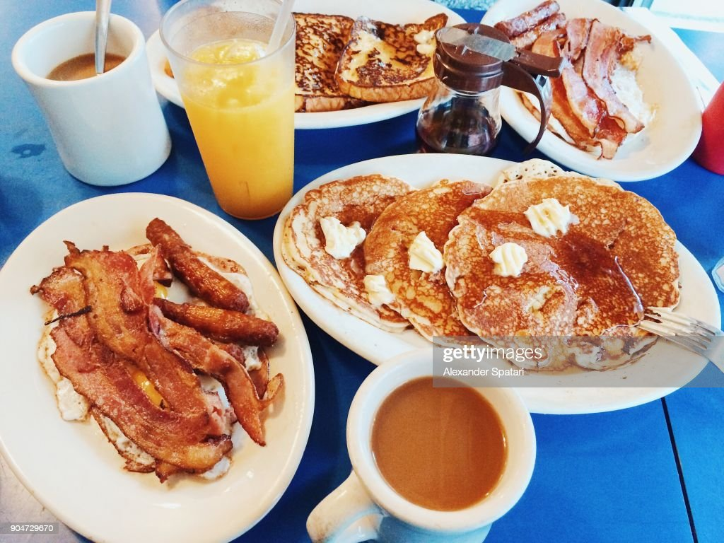 Classic American breakfast with fried eggs, bacon, pancakes, maple syrup and coffee served in a diner : Stock Photo