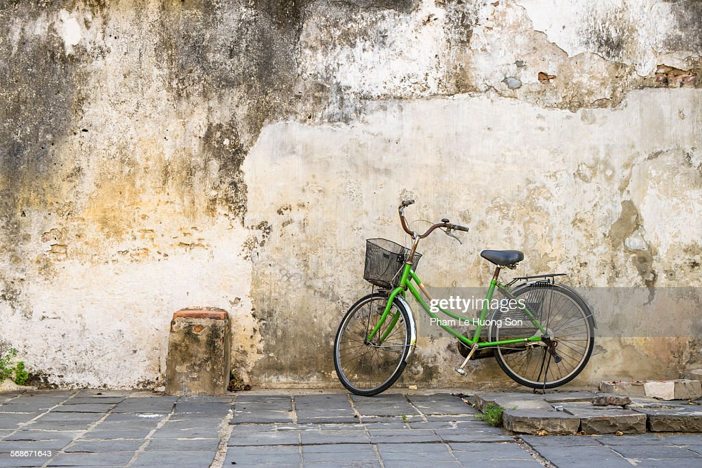 Classic bicycle leaned on the old and damage wall : Stock Photo