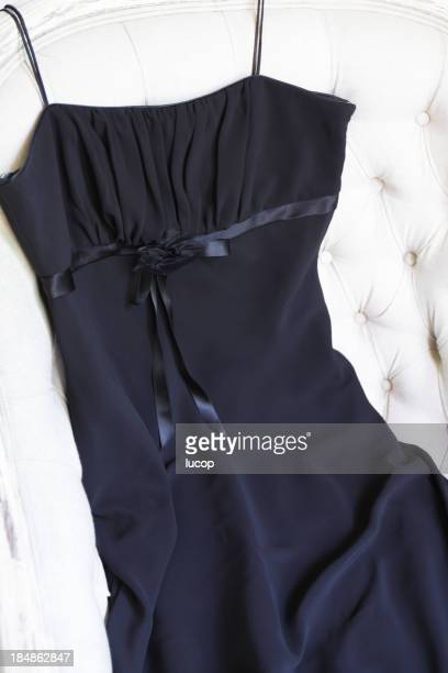 Classic black dress on a white armchair