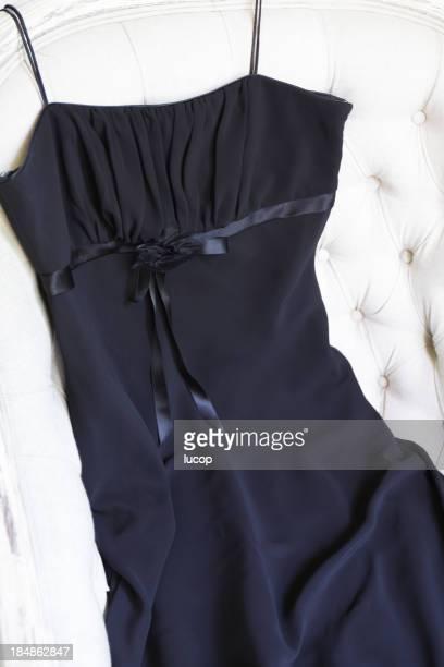 Klassische schwarze Kleid auf einem weißen Sessel