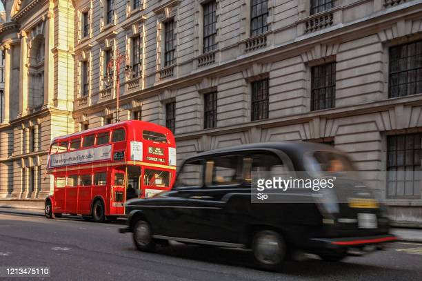 """classic black london cab driving past a classic london double decker bus in the city of westminster, london - """"sjoerd van der wal"""" or """"sjo"""" stock pictures, royalty-free photos & images"""
