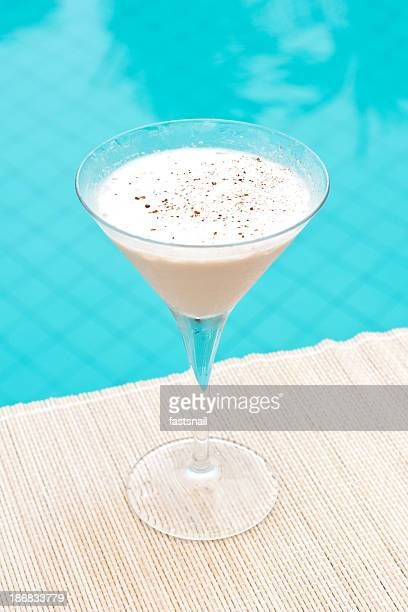 Classic Brandy Alexander cocktail near waterpool on the mat