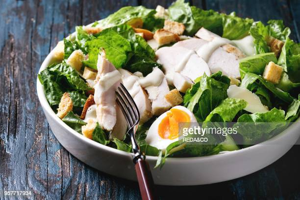 Classic Caesar salad with grilled chicken breast and half of egg in white ceramic plate. Over old dark blue wooden background. Close up. Rustic style.