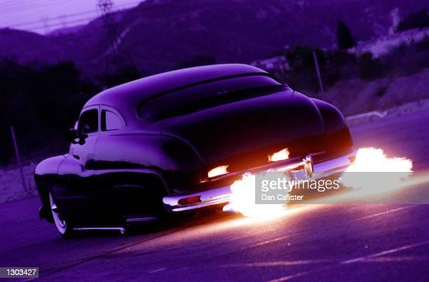 Classic car designer and builder Dean Bryant drives his customized flame blowing 1950 Mercury down a street June 19 2000 in Santa Clarita Ca Between...