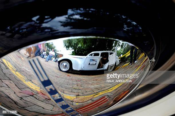 A classic car is seen reflected on a hubcap during a classic car parade in the framework of Flower Festival in Medellin Antioquia department Colombia...