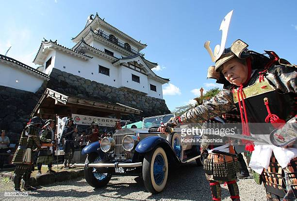 Classic car owners drive their vintage automobiles past the crowds during the 2008 La Festa Mille Miglia classic car rally at the Shiroishi Castle on...