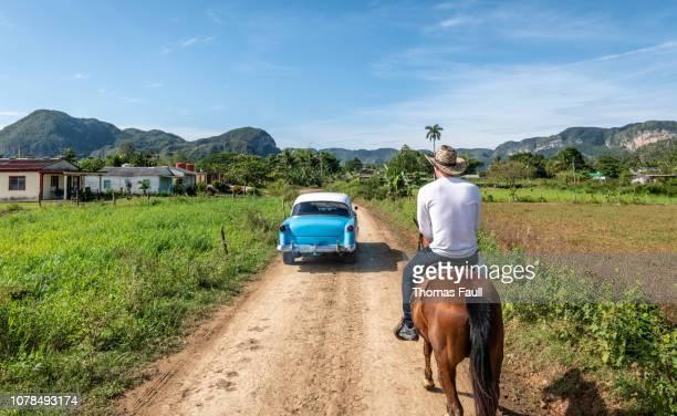 coche clásico pasa a un hombre a caballo en viñales, cuba - cuba fotografías e imágenes de stock
