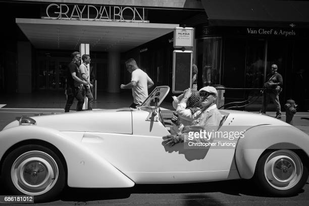 A classic car promoting a beach party drives along the Boulevard de la Croisette during annual Cannes Film Festival at Palais des Festivals on May 20...